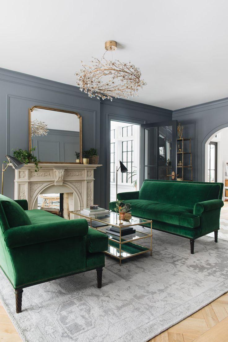 Jean Stoffer Design | Transitional living room: mid/dark grey walls, wall panels, antique gold-framed mirror on mantel, velvet deep green sofas, gold accents