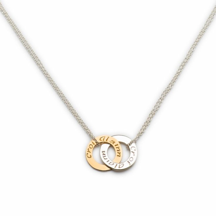 "A sweet pendant linking a gold and silver circle. It is inscribed with 'Croí álainn' meaning 'A beautiful heart' on both sides of the circles. The piece includes an extension chain at the back that allows it to be worn at various lengths. Sterling Silver. 9ct Gold Length: 30mm. Chain: 42-45cm /16""-18"" length (adjustable extension chain)   Available Here: http://www.standun.com/enibas-croi-alainn-double-mini-pendant.html"