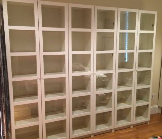 Six white Billy bookcase units with glass doors and
