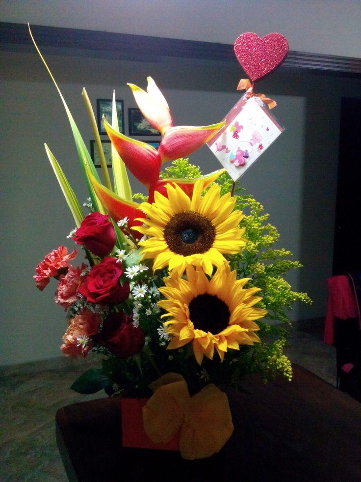 Arreglos florales, girasoles, rosas rojas, claveles rosados, heliconia, solidago, asper blanco.