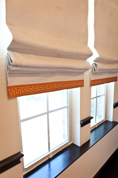 canvas or linen roman shades with accent trim at bottom. hang in area between ceiling and top of window so when pulled up they do not cover glass.