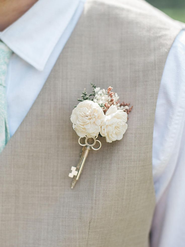 Fashion a simple rustic boutonniere with flowers and an antique key for a unique, shabby-chic groom accent.