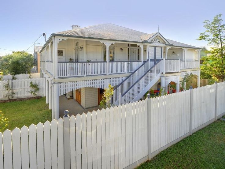 White and light grey picket fence and behind the fence a white Queenslander. #fence #white #queenslanderhome