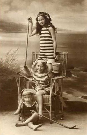 Three little girls in swimsuits getting a portrait likely in a photographer's place next to the sea or on a boardwalk. Copyright free antique image.