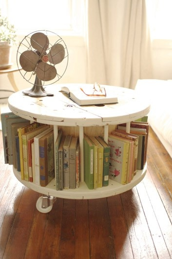 This is a great idea!  You take an old wooden spool used for wiring (you can sometimes get them for free from your local cable or telephone company), add partitions, paint it white, put it on wheels...and you have yourself a rolling coffee table where you can store books!  Cool!!!