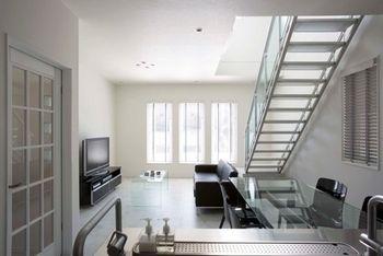 オープンLDKで、開放的なKさん邸。白で統一した空間に、自然光がやわらかく反射し、Kさんこだわりのソファやテーブル、キッチンなどが映える。また、照明はダウンライトにして凹凸のない空間に。ドアはガラス、テーブルもガラス、スケルトン階段にして、全体的に開放感を演出している