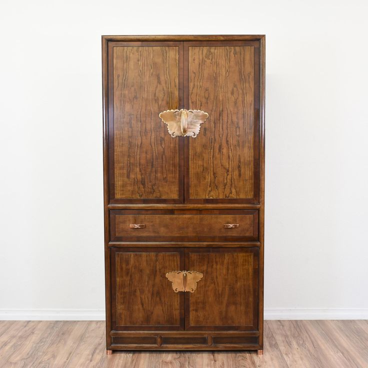 "This ""Henredon"" wardrobe cabinet is featured in a solid wood with a glossy 2 toned oak finish. This tall dresser armoire is in great condition with 4 large drawers, a large interior cabinet with shelving and unique brass hardware. Regal storage piece perfect as an entertainment center! #asian #dressers #armoireorwardrobe #sandiegovintage #vintagefurniture"