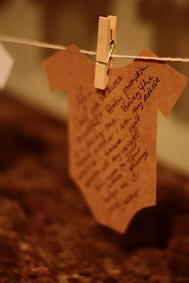 guests write words of wisdom on little baby onesies and clipped them on a clothes line. Cut the onesies out of white cardstock, and kraft paper and hang on a twine with baby clothespins from Michael's