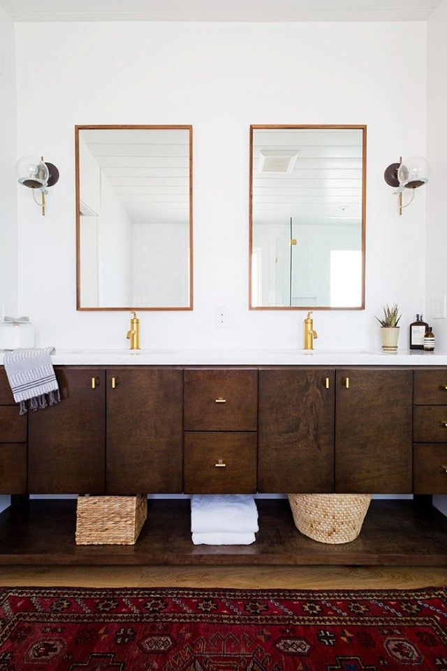 Contemporary bathroom with a dark wood floating double vanity, matching mirrors, and a sconce