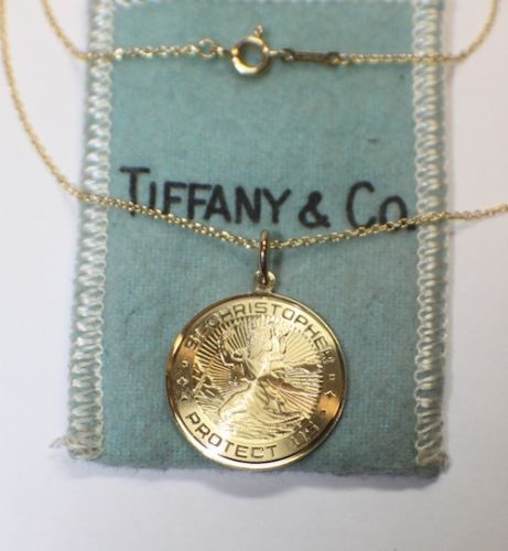 """Beautiful Tiffany & Co. Necklace and St. Christopher Pendant. """"St. Christopher Protect Us"""" decorating the gold coin. Chain is 18 inches, pendant is 22mm. Classic blue Tiffany pouch included."""