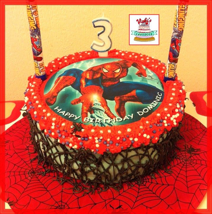 round spiderman cake with icing webbing on a web decorated board with fountain candles Spiderman Cake