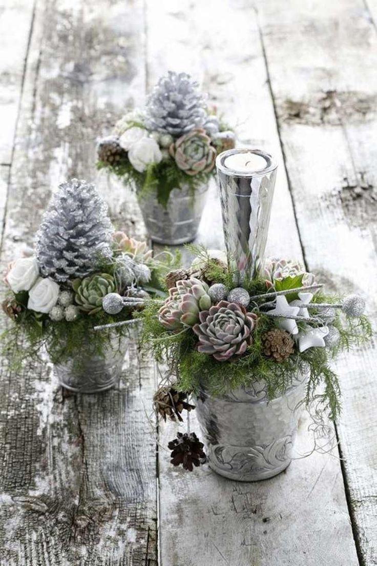 de petits arrangements en succulentes, pommes de pin saupoudrées de paillettes argentées et roses blanches en tant que déco de table pour Noël