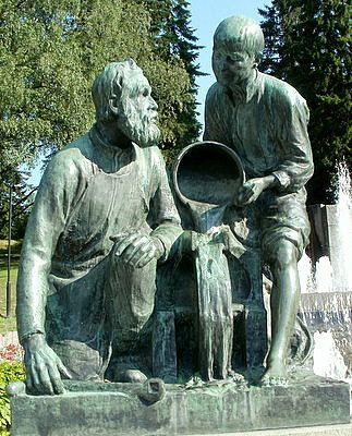 """Näsinpuisto, Tampere. - Näsikallion suihkukaivo monumentti (1913, Emil Wikström). Toinen etualan veistosteoksista on kunnianosoitus Tampereen tehdasteollisuudelle, kuvaten, Emil Wikströmin vuodelta 1913 olevan lehtihaastattelun mukaan """"poikaa joka näyttää isälleen, kuinka ratas pyörii pelkän veden voimalla ja isä, joka koko ikänsä, on saanut ratasta käsin vääntää, laskee hämmästyneenä kampinsa kädestään."""" Kuva: matkailu-opas"""