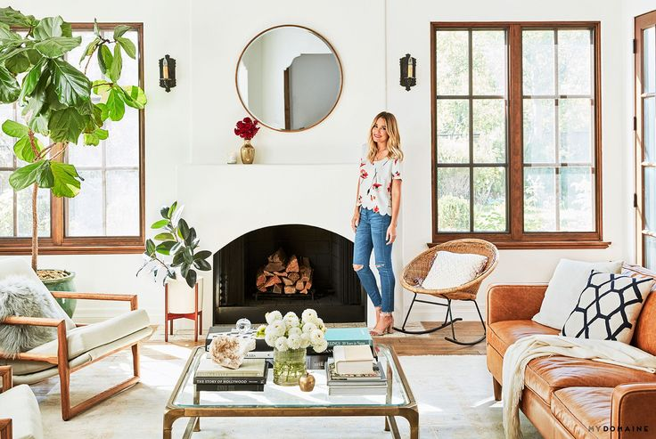 Lauren Conrad's bright and airy living space with a fireplace, a camel leather sofa,  a fireplace, a round mirror, and a rattan chair
