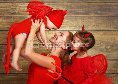 Счастливая семья с дьяволом костюмы готовит для Хэллоуина — стоковое изображение #122411408