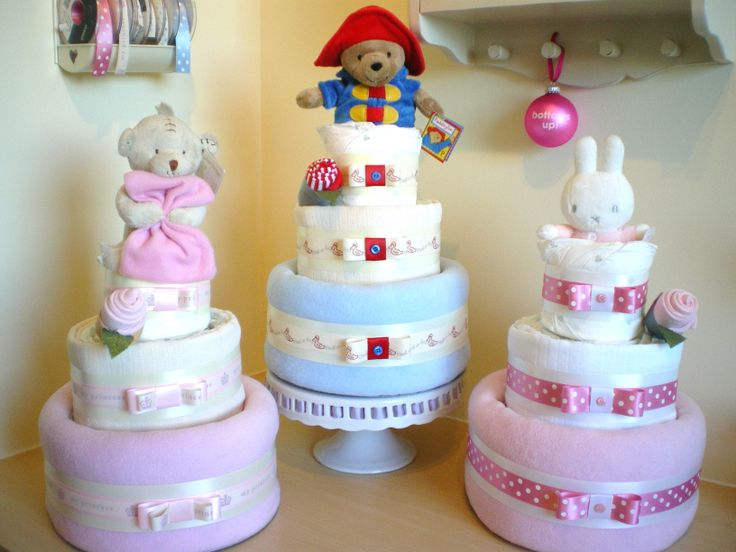 A trio of 3 tier nappy cakes with various toppers.