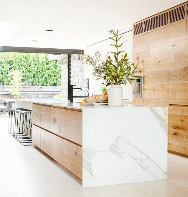 A wood-grain and white marble island has an organic, earthy air in this bright kitchen.