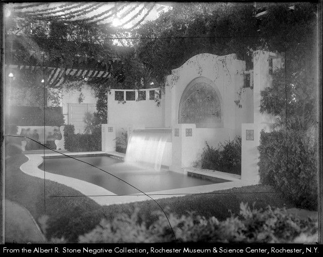Convention Hall fountain displayed by the City Parks Department at the annual show of the Rochester Florists' Association. A group of people are sitting on a bench far left.
