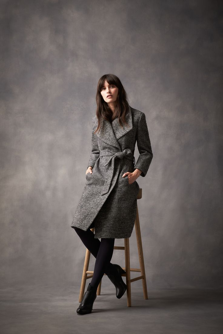 A chevron texture coat cut in a straight fit with a wide lapel, concealed press-stud fastenings and a belt to tie at the waist.