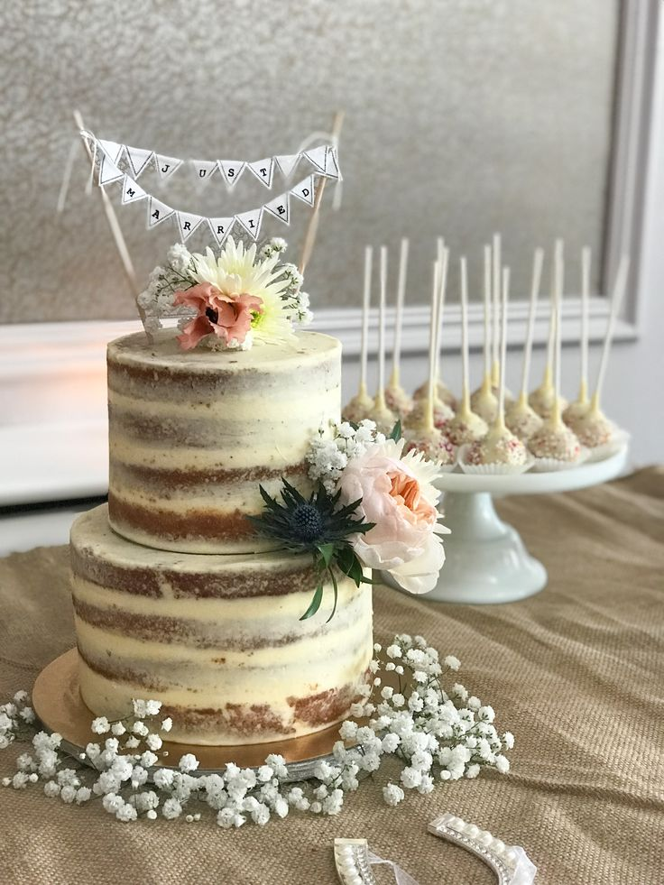 Pretty semi naked cake with fresh blooms and bunting.