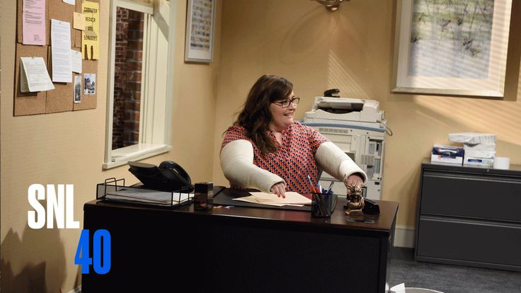 Three coworkers (Bobby Moynihan, Dakota Johnson, Cecily Strong) just can't even when it comes to their coworker Margo (Aidy Bryant) and her two broken arms. ...