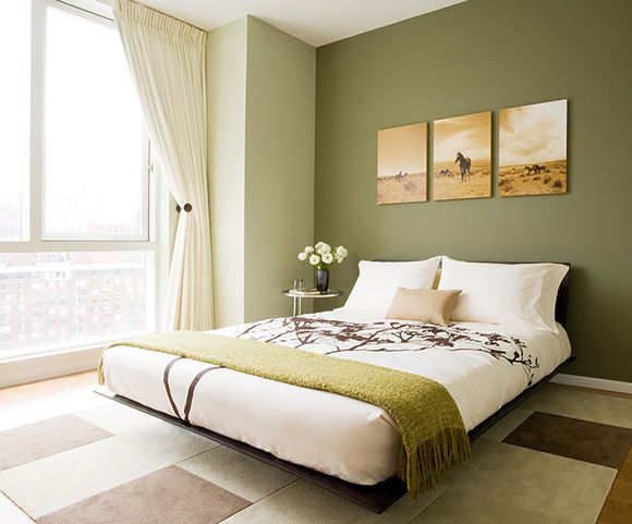 It's all about the different tones of green in this tranquil bedroom! Black zen platform bed, cream cotton drapes panels and wool rug.  green brown orange bedroom colors.