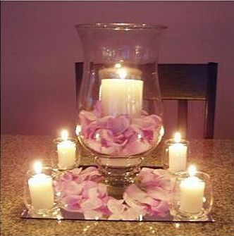 This is another easy centerpiece arrangement. All you need for this one is a pretty vase & pillar candle for center, rose petals, and the smaller vases and candles to go around it. The mirror adds a dramatic and elegant touch!
