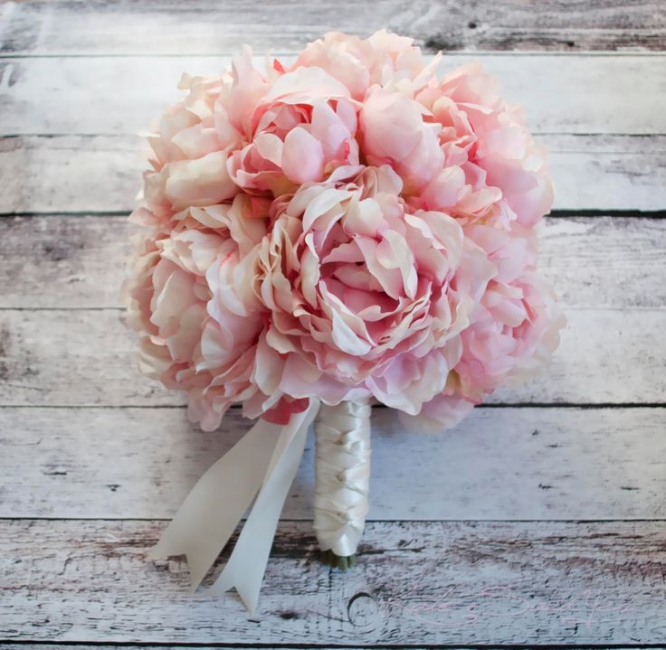 This Pink Peony Bouquet is large, romantic, and elegant. Soft blush pink silk peony blooms are tied and braided with ivory satin ribbon to make a truly beautiful peony wedding bouquet. This bouquet me