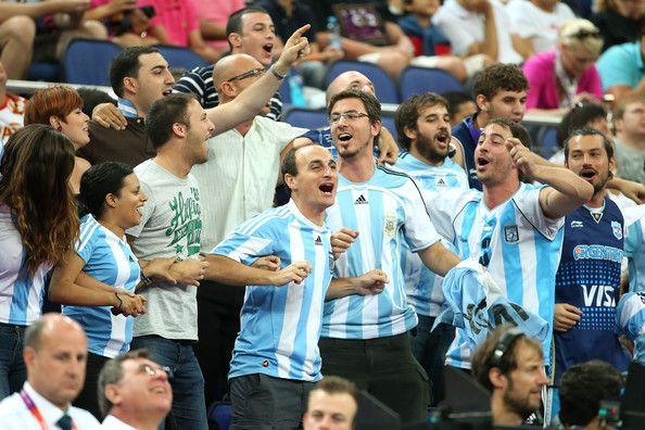 Estos son los seguidores del equipo de baloncesto de Argentina. Están animando para el equipo de baloncesto de Argentina en los Juegos Olímpicos. Están usando la ropa argentina para apoyar a su equipo.
