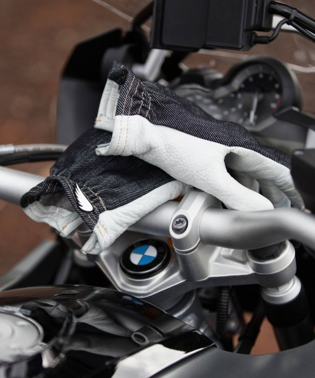 The ultimate moto glove collab. Flawlessly constructed from Saint's unbreakable motorcycle denim, we blend cotton with Dyneema® - result - the Saint denim is 750%* stronger than regular denim, demonstrating significant burst and abrasion resilience. The inner is 100% wool and the palms are buttery soft white tanned deerskin. The glove is finished off with our signature Saint wing pin.  The result a badass looking, do-everything, lined glove that is just about impossible to rip.