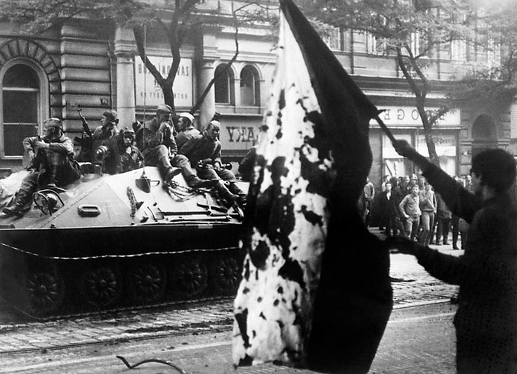 Prague, Czechoslovakia. 1968. A Czech holds a blood stained flag as a Soviet tank drives by.