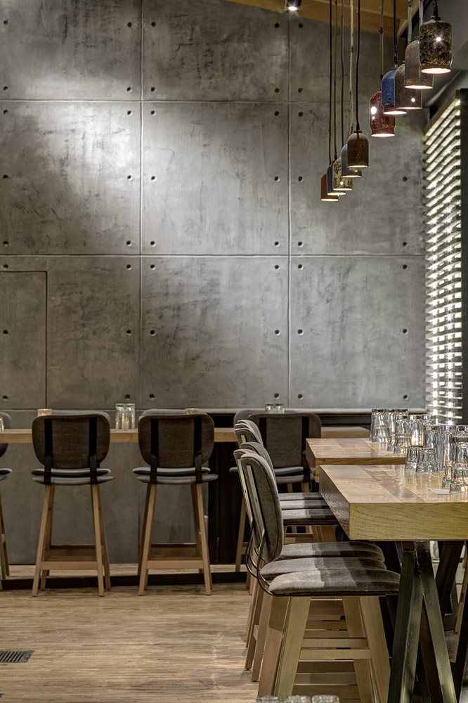 bar height tables, pendant lights, concrete wall,