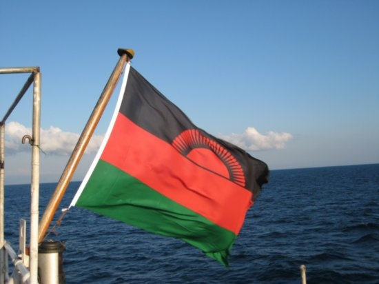 malawi flag - the malawi flag features a black stripe that represents the people of africa. the color red stands for the blood spilt in malawi's struggle for independence; while the color green symbolizes the country's vegetation. the rising sun represents the dawn of freedom and hope on the african continent