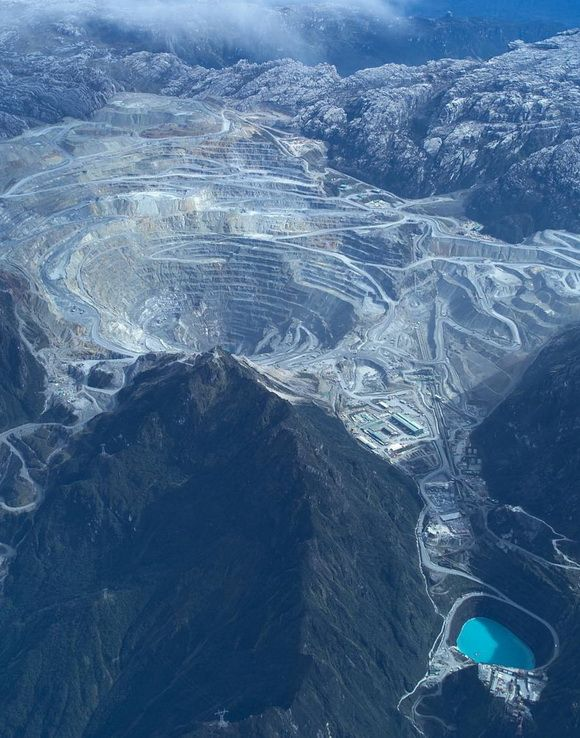 The Grasberg Mine is the largest gold mine and the third largest copper mine in the world. It is located in the province of Papua in Indonesia near Puncak Jaya, the highest mountain in Papua, and it has 19,500 employees. - http://www.theworldgeography.com/2013/06/earth-scars.html