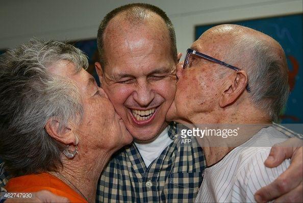 News Photo : Al-Jazeera journalist Peter Greste is kissed by...