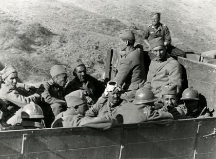 Tweede Wereldoorlog. Soldaten in de bak van een vrachtwagen. Eén van hen is gewond aan zijn hoofd. Griekenland, Kreta,1941. [Mogelijk Griekse krijgsgevangenen, sommigen met helm in Fanse stijl. Op de achtergrond een Duitser].    Second World War. Soldiers in the trunk of a truck. One of them has a headwound. Greece, Crete, 1941. [Probably captured Greek soldiers. Some of them are wearing the old French-style helmet. The guy in the background is a German].