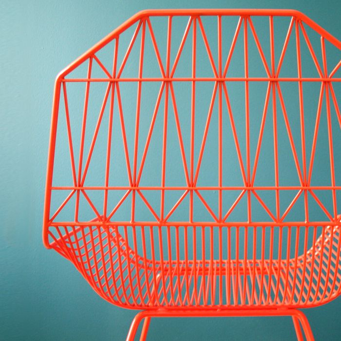 """Modern as the geometry of this chair suggests, designer Gaurav Nanda also took inspiration for the backrest from structural design of old Amish barns. Each piece is machine-molded and undergoes upwards of 400 handmade spot-welds—a process Gaurav refers to as """"bending."""" Each bend is carefully arranged to ensure structural strength, while the angles of the back, the curves of the seat, and the closeness of the wires are designed to encourage relaxation, comfort"""