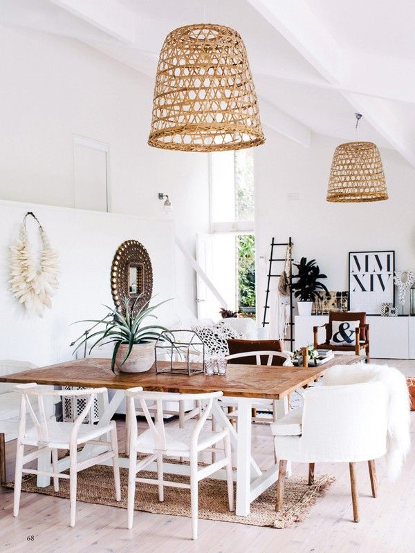 This beachy beauty features luxe accents like vintage leather accent chairs and beautiful woven overscale pendant lights. The unique wall hanging looks like a piece of statement jewelry and helps to demarcate the dining room from the adjacent sitting area. An eclectic collection of table décor keeps things casual.