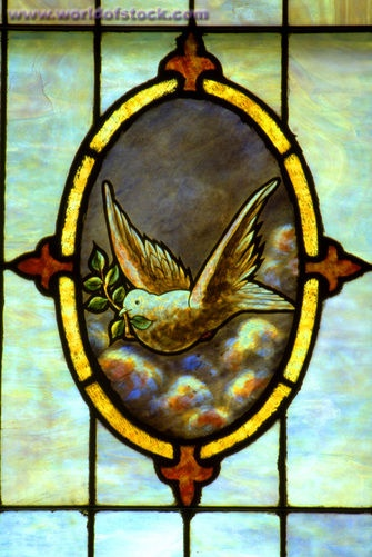 Stained glass depicting a dove carrying an olive branch.