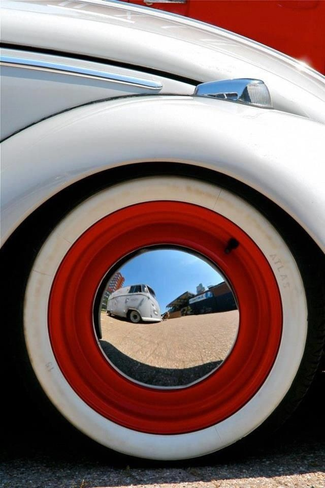 red vw wheel with white wall tire and chrome baby moon hubcap