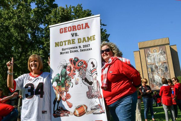 Sep 9, 2017; South Bend, IN, USA; Emily Buck, left, and Wendy Silvius, from Atlanta, pose for photos in front of the Word of Life mural, commonly known as Touchdown Jesus before the game between the Georgia Bulldogs and the Notre Dame Fighting Irish at Notre Dame Stadium. Mandatory Credit: Matt Cashore-USA TODAY Sports