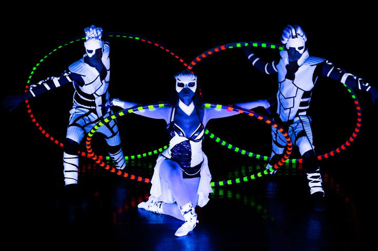Cyr Wheel performers trio under black (UV) light. Two boys, one girl in Crystal Light Show. http://antaagni.com/crystal-light-show/