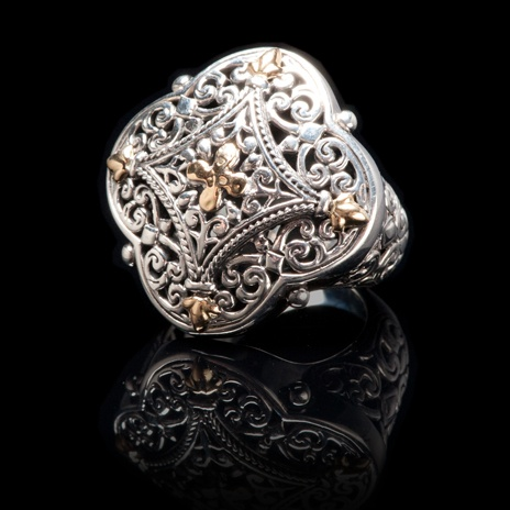 Balinese Style Ring    Sterling silver and gold Balinese style ring with intricate scroll design work in sterling silver and 18 karat yellow gold accents. The shoulders of the ring have filigree work continuing the Balinese design. Underneath it all, in the under gallery, is a pattern of scroll work adding to the superior craftsmanship and design of this striking ring.