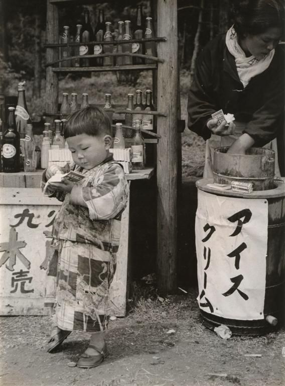 Very dirty little boy in kimono by a beverage stand. 1970s by Yahagi Koichiro. Japan.