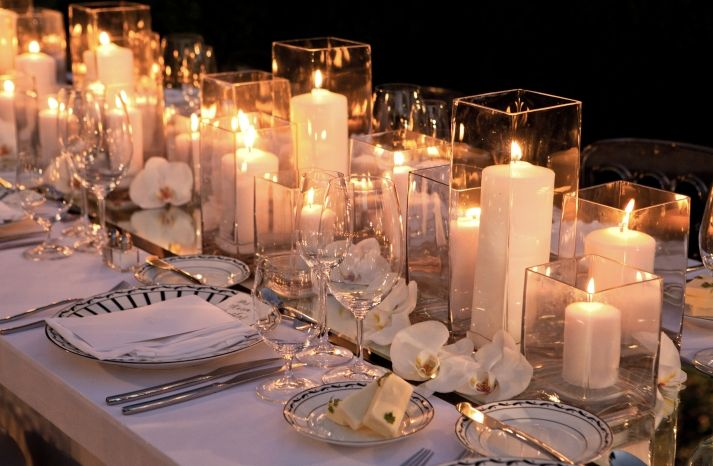 Candles as centerpieces w lots of glass holders and