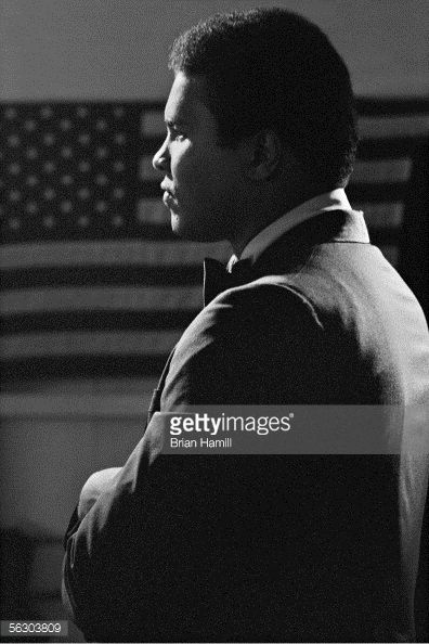American heavyweight boxer Muhammad Ali looks to the side before a large American flag late 1960s