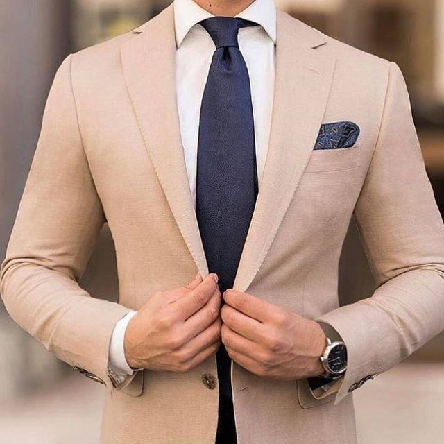 Beige blazer, white dress shirt, and dark tie and pocket square to contrast