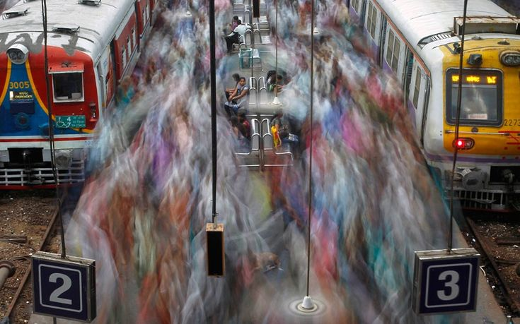 11 July 2012: Commuters disembark from crowded suburban trains during the morning rush hour at Churchgate railway station on World Population Day in Mumbai, India