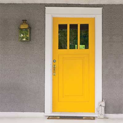 A bold yellow front door gives visitors a cheery welcome. | Photo: Tria Giovan | thisoldhouse.com