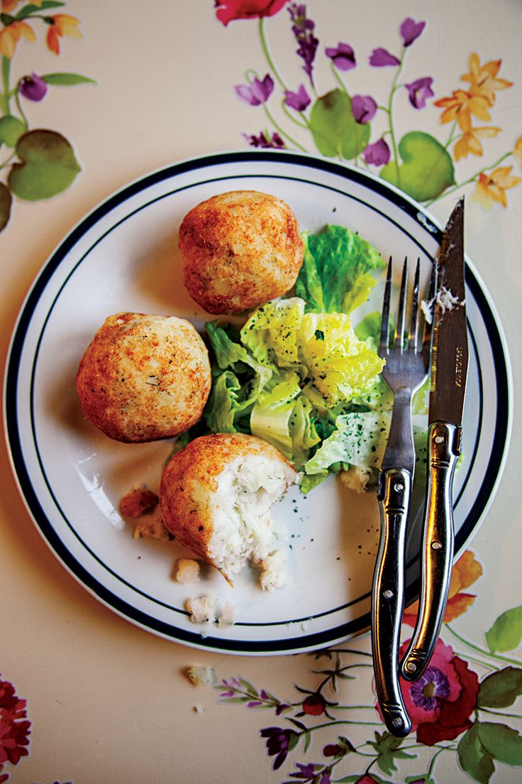 Salt cod fritters, a specialty of Saint-Pierre and Miquelon, gain herbaceous dimension from potatoes cooked in a wine-laced court bouillon.